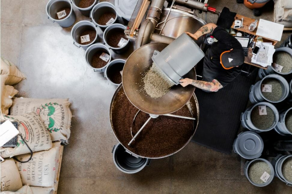 Loading the raw green beans into the hopper at Sightglass Coffee